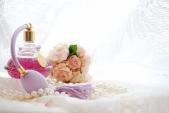Stillleben mit Weinleseparfümflasche und getrockneten rosa Rosen im Boudoirraum Stockfotografie