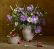 Stillleben mit Wildflowers und süßer Kirsche Stockfotos
