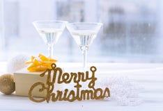 Stillleben mit zwei Gläsern, Aufschrift der frohen Weihnachten und einer Geschenkbox lizenzfreie stockfotos