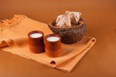 Stillleben mit zwei Schalen Milch und Keksen in einem hölzernen Vase Stockbilder