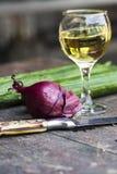 Stillleben mit Zwiebel, Messer, Wein und Gurken stockfotos