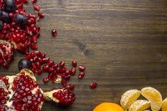 Stillleben trägt, Granatäpfel, Trauben, Mandarinen Früchte Ansicht von oben Auf einem hölzernen Hintergrund Stockbilder