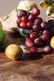 Stillleben trägt mit chinesischer Birne, Kiwi, rotem Apfel, Trauben und Cu Früchte Stockfotografie