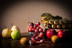 Stillleben trägt mit chinesischer Birne, Kiwi, rotem Apfel, Trauben und Cu Früchte Stockfoto