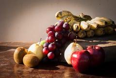 Stillleben trägt mit chinesischer Birne, Kiwi, rotem Apfel, Trauben und Cu Früchte Stockfotos