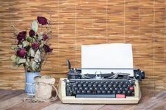Stillleben trockene Rose und Goldmünze mit Schreibmaschine Lizenzfreies Stockfoto