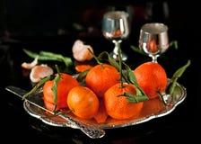 Stillleben von frischen Tangerinen mit Blättern auf einem Behälter Stockfotos
