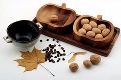 Stillleben von hölzernen Schalen, von Walnüssen, von Kaffee und von Ahornblatt auf weißem Hintergrund lizenzfreies stockfoto