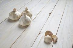 Stillleben von Köpfe und Knoblauchzehen auf einem weißen Holztisch stockbild