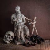 Stillleben von Moses-Statue, Schädel, hölzerne Zahl auf Matte Stockbild