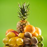 Stilllebenananas und verschiedene Früchte auf grünem Hintergrund, quadratischer Schuss Lizenzfreies Stockfoto