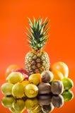 Stilllebenananas und verschiedene Früchte auf orange Hintergrund, vertikaler Schuss Stockfotografie