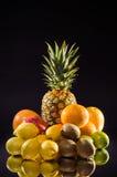 Stilllebenananas und verschiedene Früchte auf schwarzem Hintergrund, vertikaler Schuss Stockbild