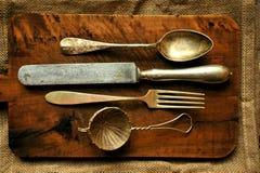 Stilllebenbild mit altem Löffel, Messer, Gabel und Sieb Stockfoto