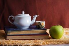 Stilllebenbuch mit Apfel- und Teeausrüstung Stockfotografie