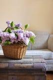 Stilllebeninnendetails, Blumenstrauß der Flieder im Korb auf Stamm Stockfoto
