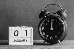 Stilllebenkonzept, guten Rutsch ins Neue Jahr durch hölzernen Kalender und Warnungscl Lizenzfreie Stockfotografie
