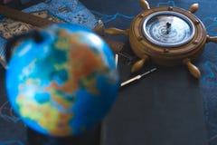 Stilllebenkugel auf einem schwarzen Matthintergrund mit einem Barometer Stockfoto