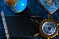 Stilllebenkugel auf einem schwarzen Matthintergrund mit einem Barometer Stockfotos