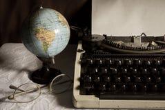 Stilllebenkugel und -brillen mit Schreibmaschine Lizenzfreies Stockfoto