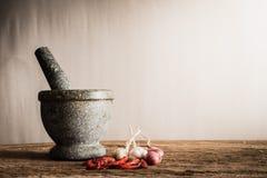 Stilllebenmörser und trockener Paprika, Knoblauch, rote Zwiebel auf hölzernem Vorsprung Lizenzfreie Stockfotos