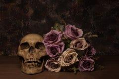 Stilllebenmalereiphotographie mit dem menschlichen Schädel und stieg anflehen an Stockfoto