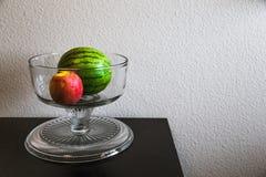 Stilllebenwassermelone und -apfel in einer Kristallschüssel auf einer Tabelle Lizenzfreie Stockfotos