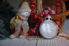 Stilllebenweinlese-Taschenuhr auf dem Hintergrund von Weihnachtsverzierungen, von brennenden Kerzen und von Tannenzweigen Lizenzfreie Stockfotografie