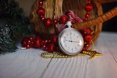 Stilllebenweinlese-Taschenuhr auf dem Hintergrund von Weihnachtsverzierungen, von brennenden Kerzen und von Tannenzweigen Stockbild