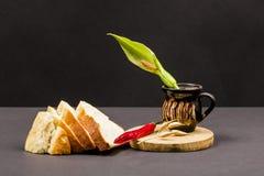 Stilllebenzusammensetzung mit hölzernem Küchenschneidebrett, Brot, roter Pfeffer und keramischer Topf mit Aronstab blühen Stockfotografie