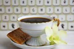Stilllife av kaffekoppen med espresso, giffel eller kex, blomma och efterföljd av tangentbordet på en träbakgrund Arkivfoto