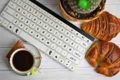Stilllife av kaffekoppen med espresso, gifflet, kexet, blomman och efterföljd av tangentbordet på en träbakgrund Royaltyfria Foton