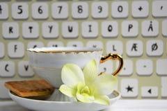 Stilllife av kaffekoppen med espresso, kexet, blomman och efterföljd av tangentbordet på en träbakgrund Royaltyfri Bild