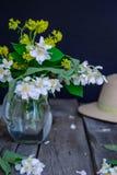 Stilllife karta z jaśminowymi kwiatami w szklanym słoju, oddzielne gałąź z kwiatami, płatki i słomiany kapelusz na drewnianym wie Fotografia Stock
