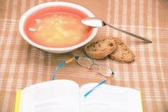 Stilllife med den soppaplattan och boken Arkivfoto