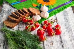 Stilllife på träbakgrund: tomater svart bröd, vitlök, f Royaltyfria Foton