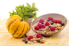 Stilllife with pumpkin, raspberries, walnuts and muesli Stock Photo