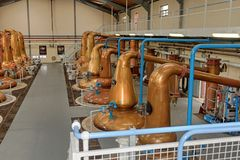 Stills for whiskey in a big distillery. Large room with distillers stills stock photography