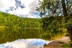 Stillsam bergsjö med reflexioner arkivbild