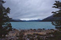 Stillsam bergsjö på en lynnig molnig dag arkivfoto