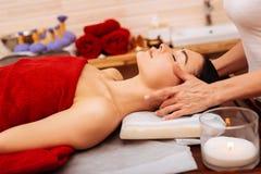 Stillsam sömnig kvinna som täckas med den röda handduken på massagetabellen arkivbilder