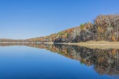 Stillsam sjö med rost färgat nedgånglandskap Fotografering för Bildbyråer