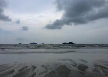 Stillsam strand med fyndsand i regnig säsong arkivfoton