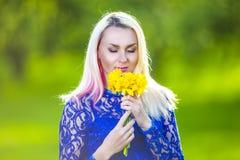 Stillsamma sinnliga Caucasian blonda lukta blommor Royaltyfri Foto
