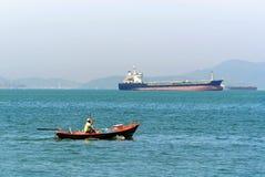 Stillsamt landskap av fiskaren på det lilla fartyget med den stora nautiska skytteln i avlägset arkivfoto