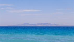 Stillsamt landskap Havsyttersida och berg på bakgrunden arkivbild