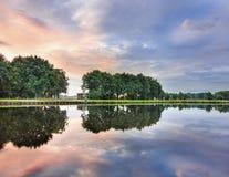 Stillsamt landskap med en kanal, träd, en mångfärgad himmel och dramatiska moln, Tilburg, Nederländerna Royaltyfri Foto