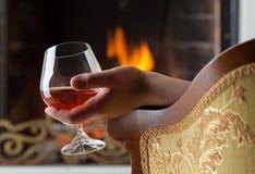 Stillstehen am brennenden Kaminfeuer mit einem Glas lizenzfreies stockbild