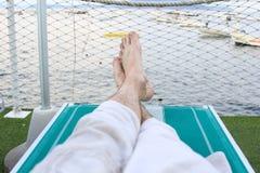 Stillstehende Füße auf einem Strand-Stuhl Stockfoto