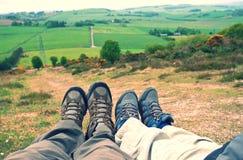 Stillstehende Kinder- und Erwachsenfüße nach Hügel gehen Stockfotografie